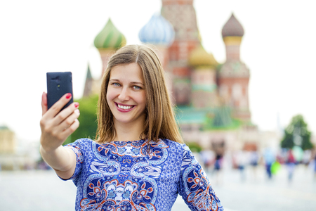 red square: Selfie, Young beautiful girl photographed on a cell phone in red square, Moscow, Russia Stock Photo