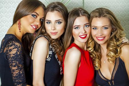 Feche acima do retrato de quatro belas mulheres jovens glamourosas no estúdio