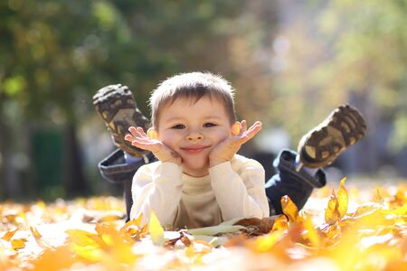 5 years old: 5 years old child lying on the golden leaf Stock Photo