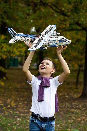 boy little: Portrait of a pretty brunette little Boy holds plastic model airplane in autumn park