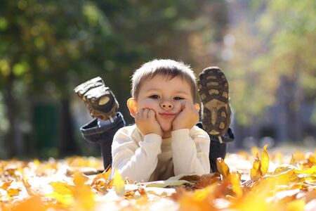 child laughing: 5 years old child lying on the golden leaf Stock Photo