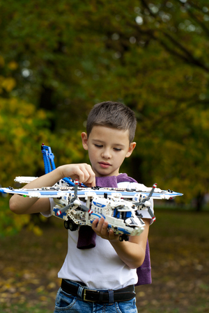 model airplane: Portrait of a pretty brunette little Boy holds plastic model airplane in autumn park