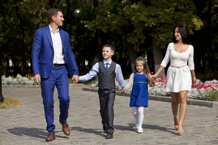 father and son holding hands: Young happy family walking in autumn park Stock Photo