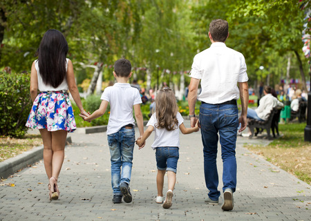 holding back: Young happy family walking in autumn park Stock Photo