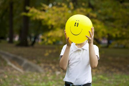 one child: Smiley. A boy holding a big yellow balloon in autumn park