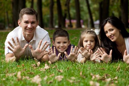 Retrato primer plano de la familia feliz acostado en el jardín en el fondo del parque del otoño