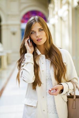 vestido blanco: Beautiful young woman in white dress walks in the shop Foto de archivo