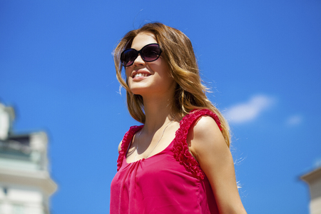sunny day: Young beautiful blonde woman in sunglasses, against the blue sky on a sunny day