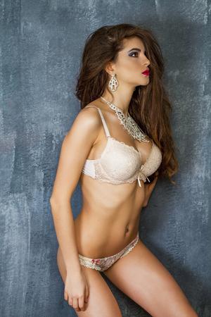 nude woman sexy: Portrait of sexy brunette woman in beige underwear on a dark wall