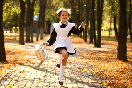 russian girl: Happy little schoolgirl run home from school, outdoor autumn park