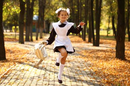 colegiala: Poco descuidado Colegiala feliz de la escuela, el oto�o de parque al aire libre Foto de archivo