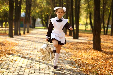 young schoolgirl: Happy little schoolgirl run home from school, outdoor autumn park
