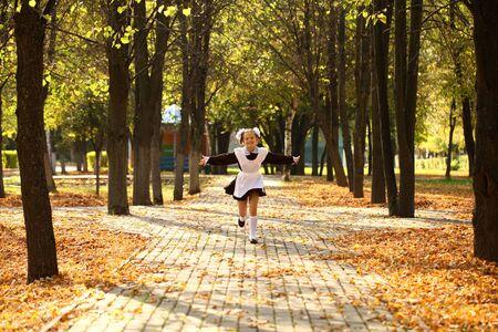 niños rubios: Poco descuidado Colegiala feliz de la escuela, el otoño de parque al aire libre Foto de archivo