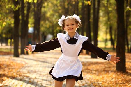 colegiala: Poco descuidado Colegiala feliz de la escuela, el otoño de parque al aire libre Foto de archivo