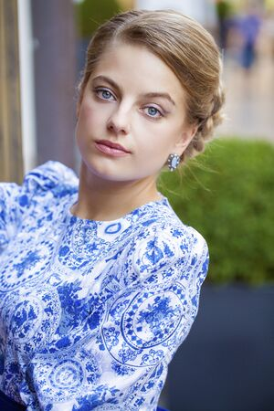bright eyed: Close up portrait of a beautiful young blonde woman in blue dress, outdoors