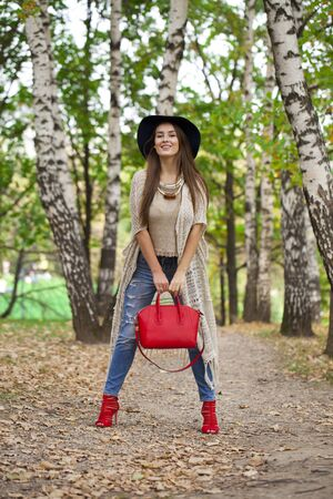 red bag: Full length portrait of a beautiful young woman in a hat and a red bag posing against a background of the autumn park Stock Photo