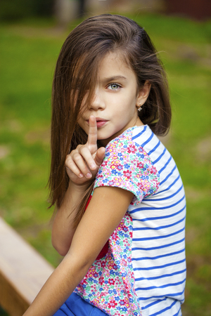 10 fingers: Young beautiful Little girl has put forefinger to lips as sign of silence, outdoors summer Stock Photo
