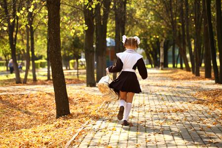 away: Happy little schoolgirl run home from school, outdoor autumn park