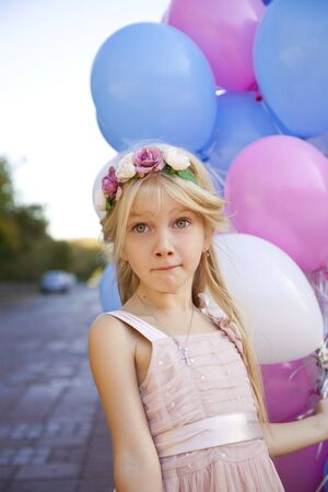 pink dress: Little five-year girl in a pink dress holding balloons, against background of summer street