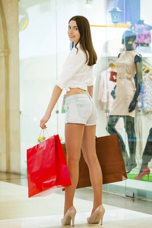 sexy jeans: Beautiful young woman in sexy jeans shorts in the shop