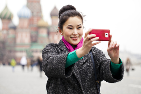 red square moscow: Young beautiful woman tourist taking pictures on mobile phone on the background Red Square, Moscow Kremlin, Russia