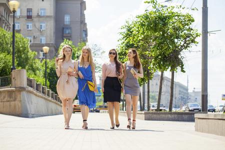 compras compulsivas: Portrait of a beautiful young four fashion women walk on summer city