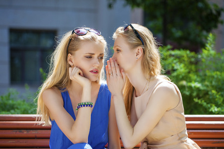 bruit: Close up portrait of Two young beautiful women secret at summer green park