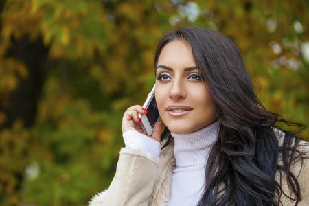 egyptian woman: Happy beautiful brunette woman calling by phone in autumn park Stock Photo
