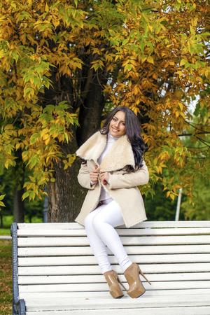sheepskin: Young beautiful arabic brunette women in white sheepskin coat sitting on a bench in the autumn park