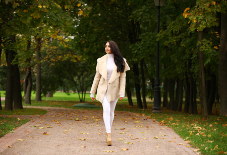 sheepskin: Young beautiful arabic brunette women in white sheepskin coat walking in autumn park