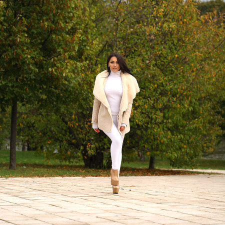 full body woman: Young beautiful arabic brunette women in white sheepskin coat walking in autumn park