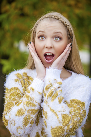 munch: Close up portrait of a young caucusian woman with blond hair scared, afraid and anxious. Screaming, with eyes wide open. Human emotions. Parody on a Munch Scream, outdoors in autumn park Stock Photo