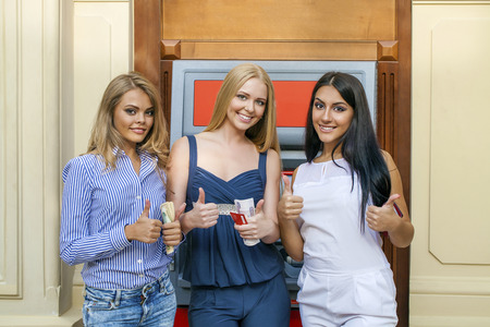 automated teller: Three young beautiful modern girls using an automated teller machine. ATM, Women withdrawing money or checking account balance