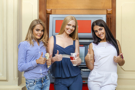 checking account: Three young beautiful modern girls using an automated teller machine. ATM, Women withdrawing money or checking account balance