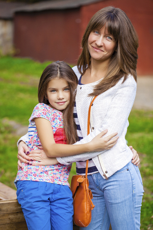 nine year old: Close up portrait of a beautiful nine year old little girl and happy mother in autumn park Stock Photo