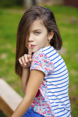 little girl child: Young beautiful Little girl has put forefinger to lips as sign of silence, outdoors summer Stock Photo
