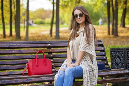 Portrait close up de la belle jeune femme blonde assise sur un banc, sur fond de parc d'automne