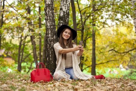 red hat: Selfie, Young beautiful woman in a hat photographing themselves on a cell phone while sitting in the autumn forest
