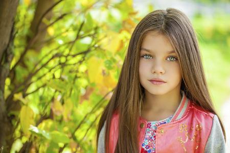 Cose вверх, Красивая девочка на зеленом фоне летнего городского парка