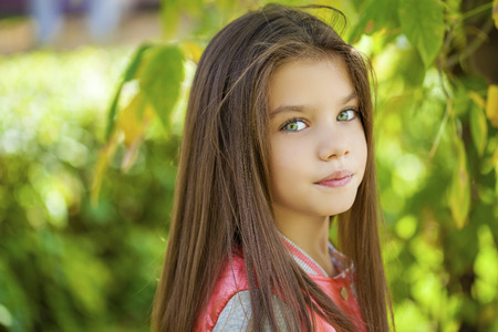 brunette teen: Cose up, Beautiful little girl on green background of summer city park