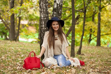 birchwood: Young stylish woman in hat resting in the autumn park on the background of a birchwood Stock Photo