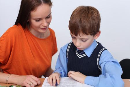 schoolwork: mother or teacher helping kid with schoolwork