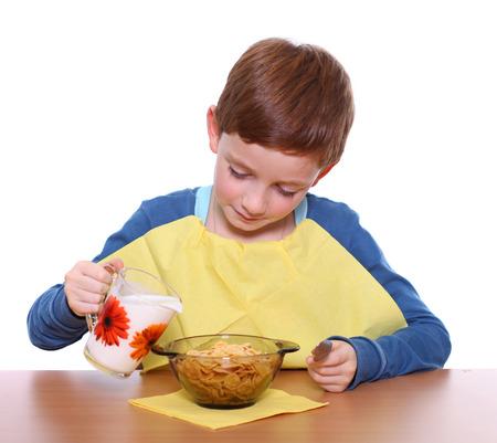 comiendo cereal: Poco desayuno niño aislado sobre fondo blanco