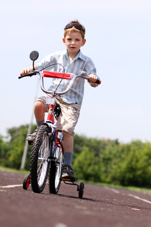 goes: little boy goes for a drive on a bicycle Stock Photo