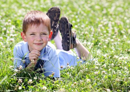 5 years: 5 years old child lying on the grass.