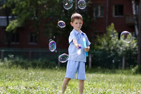 love very: little boy is played with soap bubbles in the street
