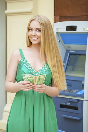 bancomat: Young beautiful woman in a green dress is holding a cash dollars on the background of the ATM in a shopping center
