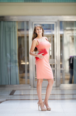 sexy pose: Beautiful young woman in pink dress in the shop