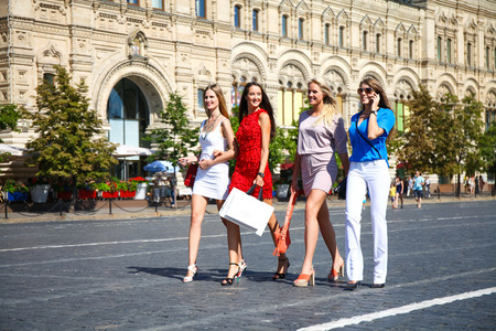 compras compulsivas: Retrato de una hermosa joven a cuatro mujeres caminan en la Plaza Roja en Mosc� Foto de archivo