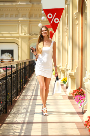 go inside: Beautiful young woman in summer dress in the shop